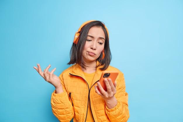 Zdziwiona, niezdecydowana azjatka patrzy na wyświetlacz smartfona, nie może wybrać piosenki do słuchania, nosi bezprzewodowe słuchawki na uszach, nosi stylową kurtkę odizolowaną nad niebieską ścianą