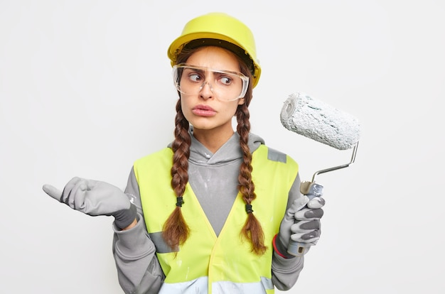Zdziwiona, niezdecydowana kobieta budowlana lub dekoratorka