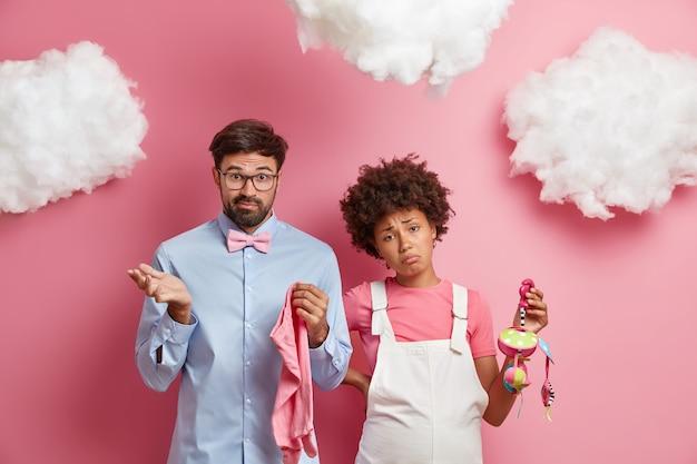 Zdziwiona, niezdecydowana niedoświadczona kobieta i mężczyzna czekają na narodziny dziecka, nie wiedzą, jakie rzeczy przygotować w szpitalu położniczym, trzymaj ubrania i zabawki dla noworodków