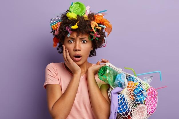 Zdziwiona, oszołomiona kobieta pozująca ze śmieciami we włosach