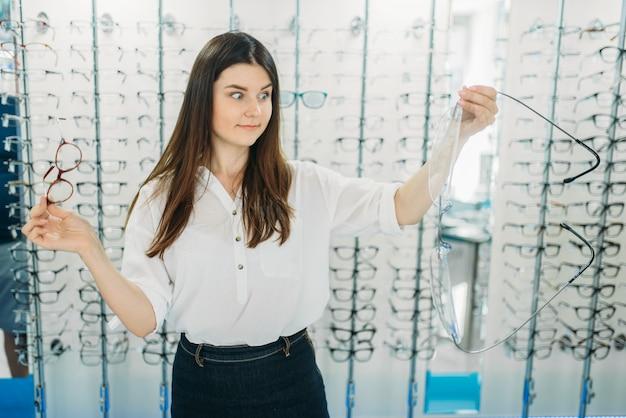 Zdziwiona pani trzyma w sklepie optycznym ogromne okulary