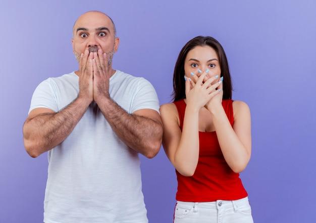 Zdziwiona para dorosłych patrząc trzymając ręce na ustach
