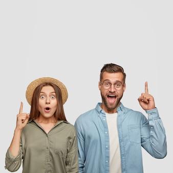 Zdziwiona piękna kobieta i przystojny wesoły zdziwiony facet wskazują razem w górę, pokazują wolne miejsce na reklamę
