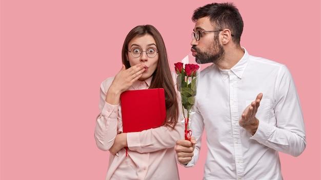 Zdziwiona piękna kobieta nie oczekuje od koleżanki kwiatów, zakrywa usta dłonią