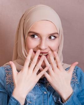 Zdziwiona piękna uśmiechnięta kobieta w hidżabie
