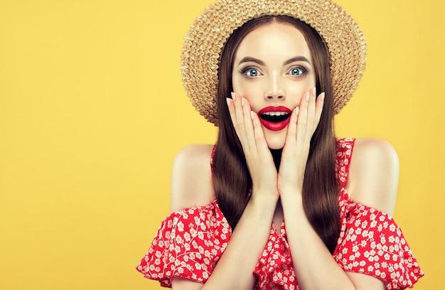Zdziwiona, podekscytowana i szczęśliwa młoda długowłosa kobieta patrzy na widzów ze zdziwieniem.