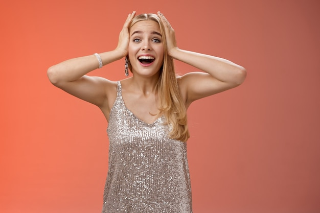 Zdziwiona podekscytowana nerwowa młoda piękna blond kobieta w srebrnej stylowej sukience nie może uwierzyć własnemu szczęściu szczęście trzymać ręce głowę uśmiechnięta krzyczeć zdziwiona pozytywna niesamowita wiadomość, triumfująca.