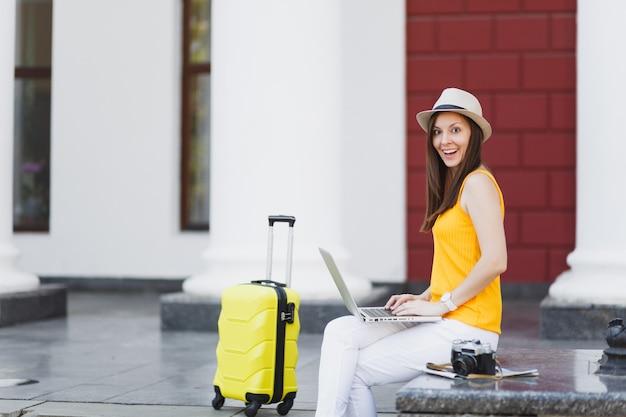 Zdziwiona podróżniczka turystyczna kobieta w ubraniach casual, kapelusz z walizką siedzieć przy pracy na komputerze typu laptop w mieście na świeżym powietrzu. dziewczyna wyjeżdża za granicę na weekendowy wypad. styl życia podróży turystycznej.