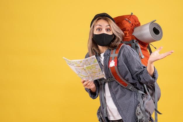 Zdziwiona podróżniczka z czarną maską i plecakiem trzymająca mapę