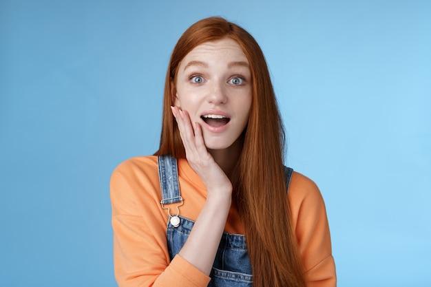 Zdziwiona przyjazna wrażliwa pod wrażeniem ruda dziewczyna uczy się niesamowitych przyjemnych wiadomości otwarte usta zdumiony uśmiechnięty zadowolony przyjaciel dotknąć policzek rozbawiony stojący niebieskie tło szczęśliwy