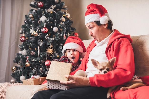 Zdziwiona rodzina w santa hat, ojciec i chłopiec dziecko otwiera prezent na boże narodzenie w domu