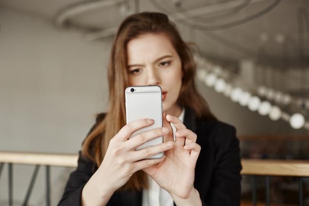 Zdziwiona, rozważna kobieta robi zakupy online za pomocą aplikacji na telefon komórkowy