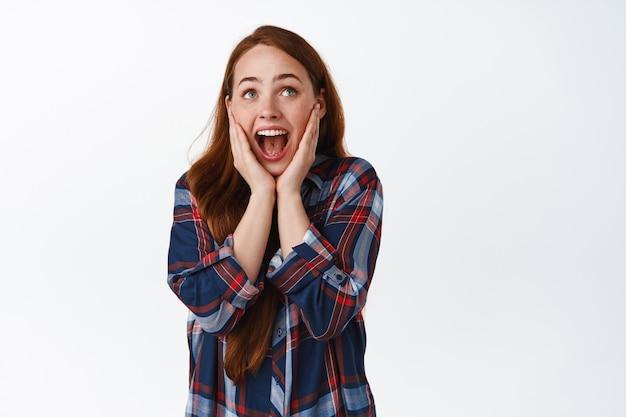 Zdziwiona ruda dziewczyna krzyczy ze zdumienia i radości, patrzy na coś niesamowitego, patrzy w górę i krzyczy szczęśliwa, ogląda telewizję, stoi na białym