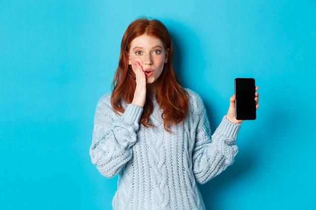 Zdziwiona ruda dziewczyna patrząca w kamerę, pokazująca ekran smartfona, pokazująca ofertę online, stojąca na niebieskim tle.