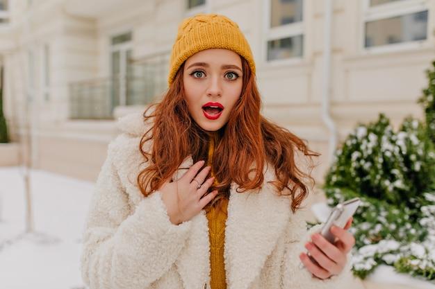 Zdziwiona ruda dziewczyna stojąca na ulicy w zimny dzień. wspaniała młoda kobieta z telefonem pozowanie na świeżym powietrzu.