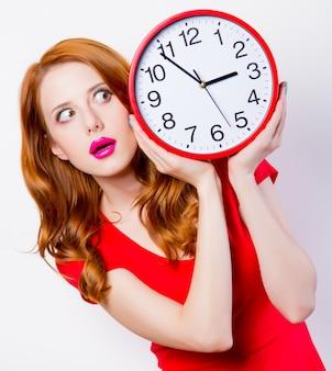 Zdziwiona ruda dziewczyna w czerwonej sukience z dużym zegarem na białym tle