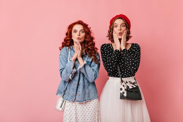Zdziwiona ruda kobieta pozuje z przyjacielem. studio strzałów dwóch dziewczyn wyrażających zdziwienie na różowym tle.