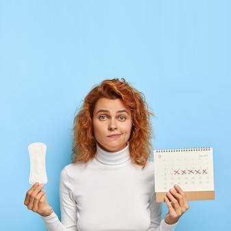 Zdziwiona ruda kobieta trzyma podpaskę i kalendarz menstruacyjny z zaznaczonymi czerwonymi dniami