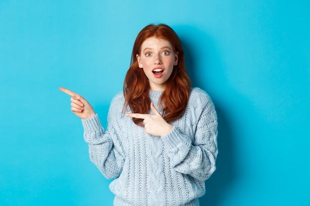 Zdziwiona rudowłosa dziewczyna w swetrze, wskazująca palcem w lewo na logo i podekscytowana wpatrująca się w kamerę, stojąca na niebieskim tle.