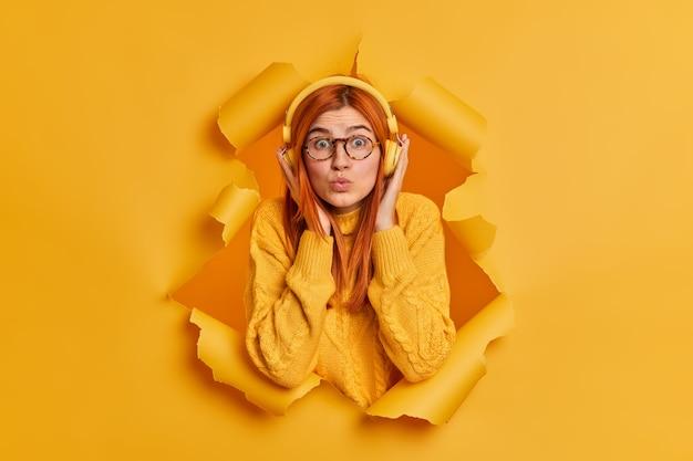 Zdziwiona rudowłosa kobieta ma zaokrąglone usta ze zdumieniem, nosi słuchawki stereo, ubrana w ciepły sweter, słucha języków obcych podczas słuchania utworów audio.