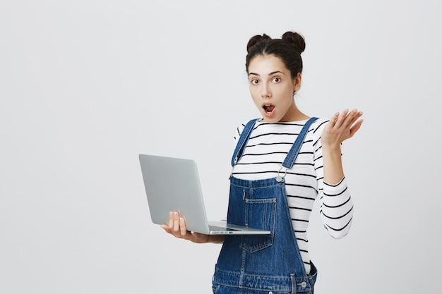 Zdziwiona śliczna dziewczyna szuka podekscytowany podczas korzystania z laptopa