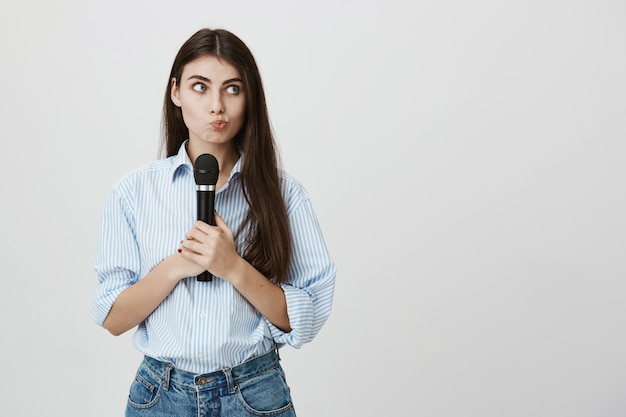 Zdziwiona śliczna kobieta dąsająca się w zamyśleniu, trzymając mikrofon