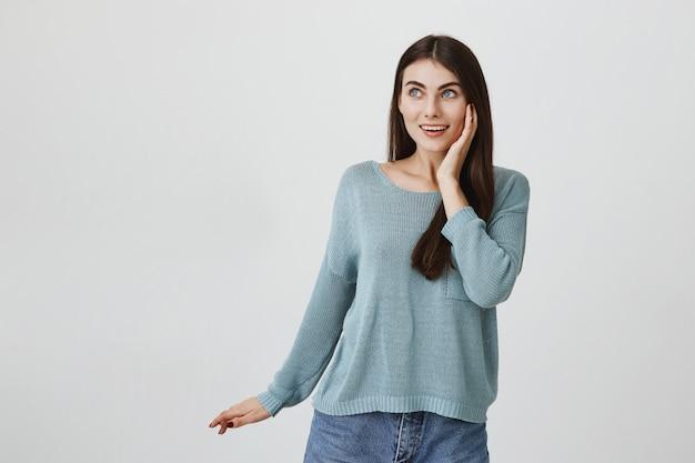 Zdziwiona śliczna kobieta uśmiechnięta, podekscytowana w lewo na reklamę