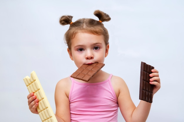 Zdziwiona śmieszna mała dziewczynka trzyma czekoladę i patrzeje.