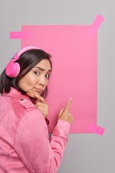 Zdziwiona smutna młoda azjatka z ciemnymi włosami wskazuje na puste puste miejsce na treść reklamową, sugeruje użycie banera promocyjnego, aby umieścić informacje, słucha muzyki w bezprzewodowych słuchawkach