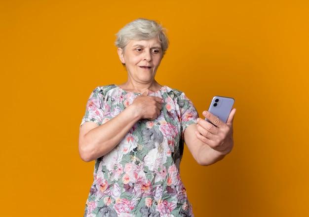 Zdziwiona starsza kobieta kładzie rękę na piersi patrząc na telefon na białym tle na pomarańczowej ścianie