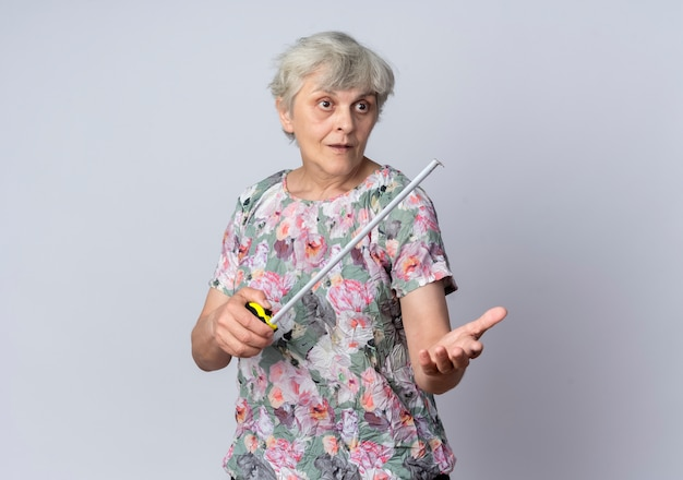 Zdziwiona starsza kobieta trzyma centymetrem patrząc i wskazując do przodu na białym tle na białej ścianie