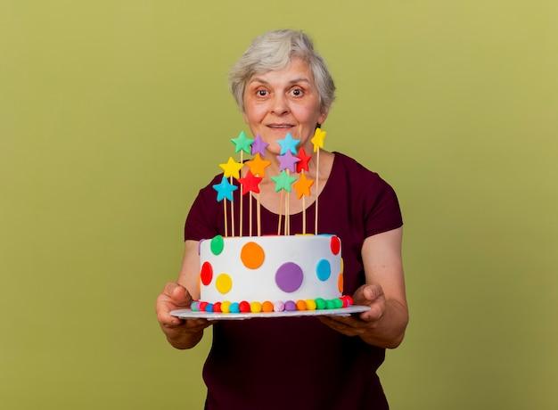 Zdziwiona starsza kobieta trzyma tort na białym tle na oliwkowej ścianie