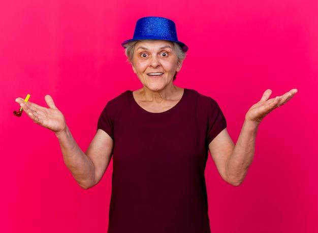 Zdziwiona starsza kobieta w kapeluszu partii trzyma gwizdek na różowo