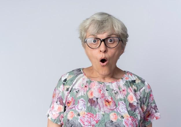 Zdziwiona starsza kobieta w okularach optycznych wygląda na białym tle na białej ścianie