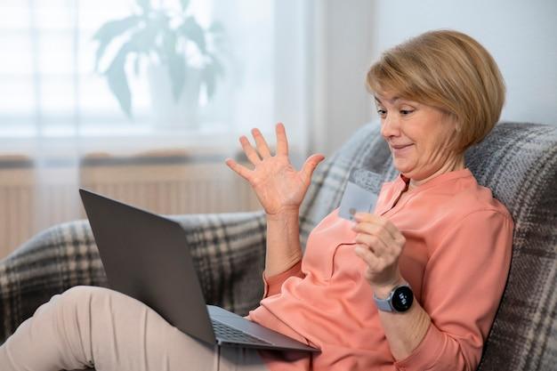 Zdziwiona starsza kobieta woła z laptopem, z kartą kredytową w ręku na zakupy w internecie