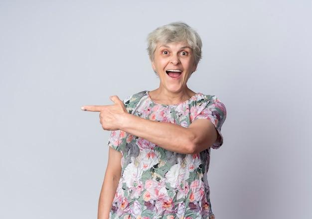 Zdziwiona starsza kobieta wskazuje na bok patrząc na białym tle na białej ścianie