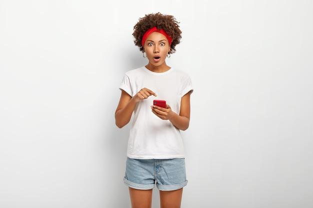 Zdziwiona studentka ma kręcone włosy, wskazuje na smartfona, robi zakupy w sieci, zaskoczona wysoką ceną czegoś