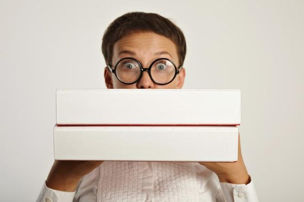 Zdziwiona studentka trzyma dwa duże foldery z planem edukacyjnym na nowy rok na uniwersytecie. skup się na folderach