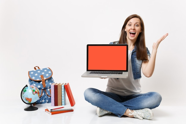 Zdziwiona studentka trzyma laptop pc z pustym czarnym pustym ekranem rozkładającym ręce w pobliżu kuli ziemskiej, plecaka, podręczników szkolnych na białym tle