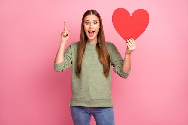 Zdziwiona szalona dziewczyna trzyma wielkie serce z czerwonej kartki papieru