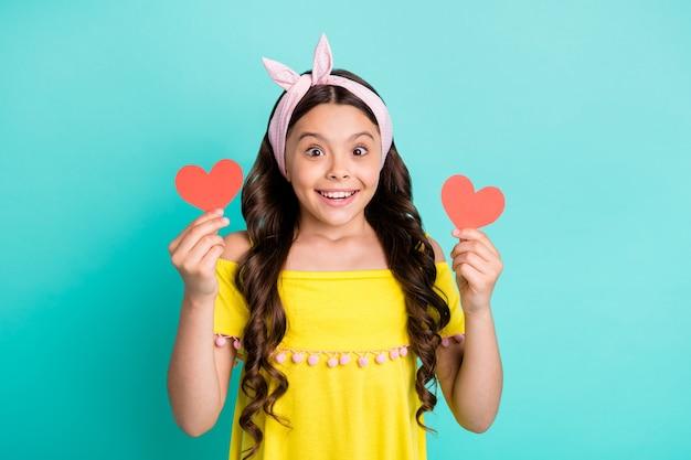 Zdziwiona szalona dziewczynka dostała małą papierową kartkę w kształcie serca pod wrażeniem twarzy