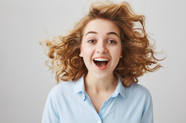 Zdziwiona szczęśliwa dziewczyna z kręconymi włosami unoszącymi się w powietrzu