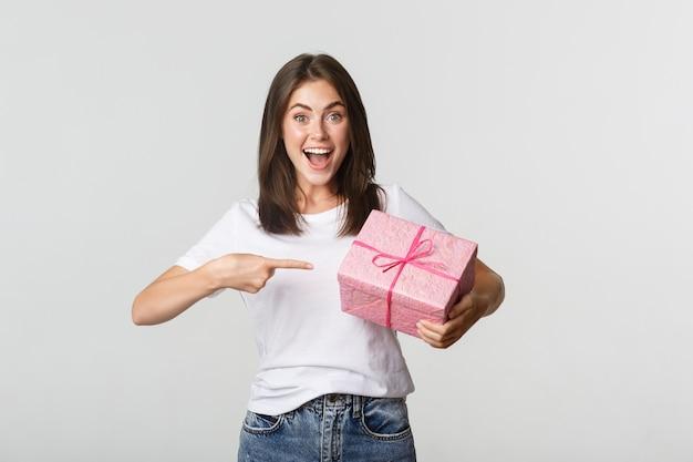 Zdziwiona szczęśliwa młoda kobieta uśmiecha się i wskazuje palcem na opakowany prezent.