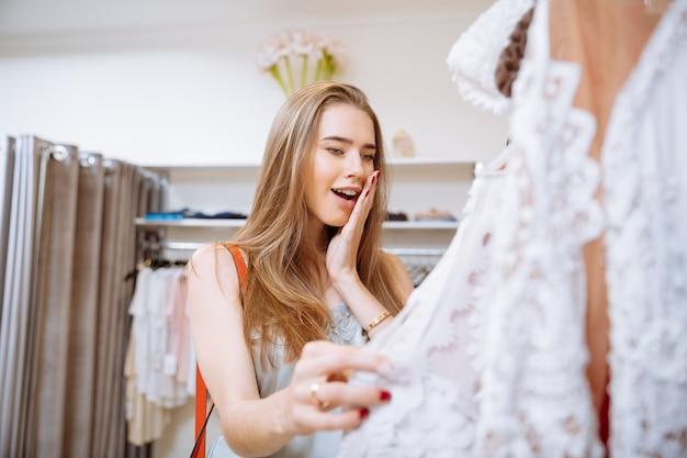 Zdziwiona szczęśliwa młoda kobieta wybiera sukienkę w sklepie odzieżowym