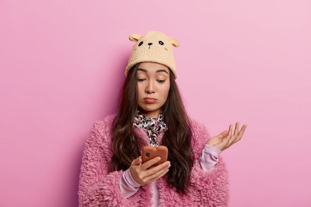 Zdziwiona tysiącletnia kobieta z oburzeniem patrzy na smartfon, czyta nieciekawy post na stronie, przegląda media społecznościowe, trzyma dłoń uniesioną do góry