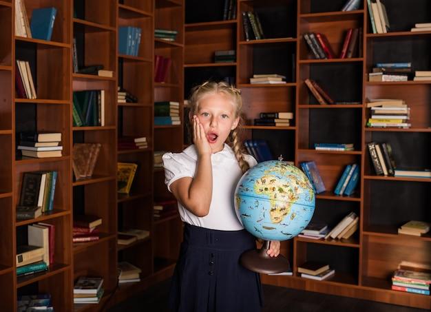 Zdziwiona uczennica w mundurku szkolnym z globusem w bibliotece