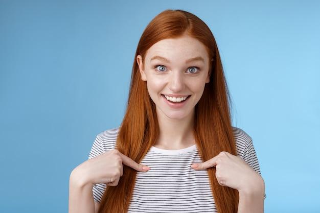 Zdziwiona uradowana podekscytowana rudowłosa dziewczyna z niebieskimi oczami wpatrzona w kamerę zafascynowana nie może uwierzyć w wygraną wskazując siebie zakwestionowana rozbawiona zdobywając nominację na pierwsze miejsce, wybrana otrzymuje stypendium.
