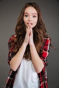 Zdziwiona urocza młoda kobieta stojąca z otwartymi ustami