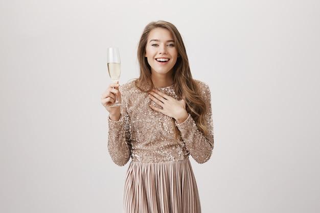 Zdziwiona uśmiechnięta kobieta w stroju wieczorowym, pijąc szampana
