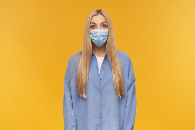 Zdziwiona wyglądająca kobieta, piękna dziewczyna o długich blond włosach. noszenie niebieskiej koszuli i medycznej maski na twarz. koncepcja ludzi i emocji. obserwując kamerę, odizolowane na pomarańczowym tle
